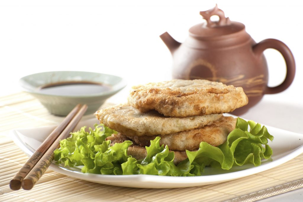 Fried chinese pancakes served with salad leaves with tea and cho